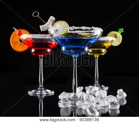 Martini drinks served on glass table with black background