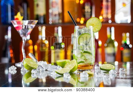 Mojito cocktail drink on bar counter with blur bottles on background