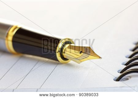 Close Up Of A Gold Fountain Pen Nib On A Notepad