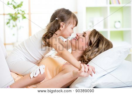 Mom and child daughter embracing and kissing in bed