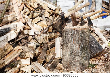 Pile Of Firewoods And Several Axes In Wooden Block