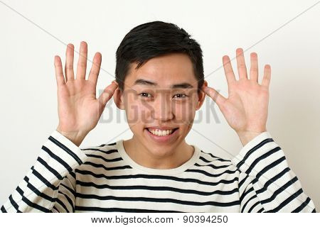 Funny young Asian man making face and looking at camera.