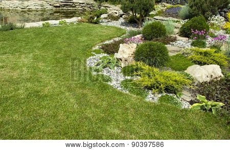 Green lawn in a colorful landscaped formal garden.Detail of a botanical garden