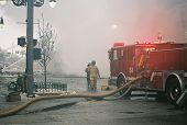 image of firehose  - fire fighters at the scene of a burning building - JPG