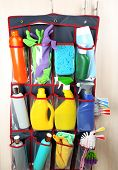 stock photo of household  - Household chemicals in holder hanging on wooden door background - JPG