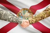 stock photo of soldier  - Soldiers handshake and US state flag  - JPG