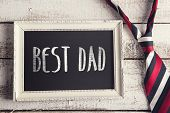 foto of tied  - Rectangle picture frame with Best dad sign and colorful tie laid on wooden floor backround - JPG