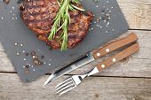 foto of ribeye steak  - Beef steaks with rosemary and spices on wooden table - JPG