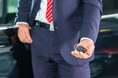 foto of showrooms  - Seller or car salesman in car dealership with key presenting his new and used cars in the showroom - JPG