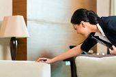 picture of housekeeper  - Housekeeping manager or assistant controlling or checking the room or suit of a hotel with a checklist on tidiness  - JPG