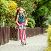foto of girlie  - Little girl with a backpack goes to school on a scooter - JPG