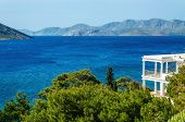 foto of greek-island  - View on the see from typical Greek appartment with clear green treens and amazing blue water and islands on horizon - JPG