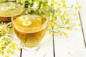 stock photo of chamomile  - cup of chamomile tea with chamomile flowers on wooden planks - JPG