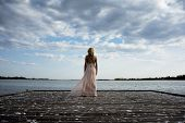 foto of evening gown  - Back potrait of beautiful blond curly woman wearing evening peach color gown at lake - JPG