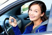 picture of driver  - Pretty female driver in a white car showing the car key - JPG