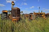 image of junk-yard  - The grill of an old rusty tractor stands out in in the long grass of a salvage yard - JPG