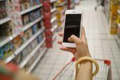 foto of supermarket  - a shopper using mobile phone in supermarket - JPG