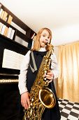 foto of saxophones  - Small girl in school uniform dress plays on the alto saxophone standing near the piano indoors - JPG