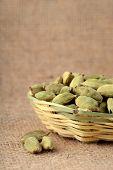stock photo of cardamom  - Green Cardamom pods in bamboo basket on sack cloth - JPG