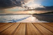 stock photo of cloud formation  - View along West coast of Wales towards beautiful sunset with sunbeams and stunning clouds formations with wooden planks floor - JPG