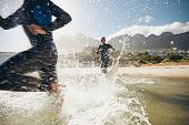 picture of triathlon  - Image of triathletes rushing into the water - JPG