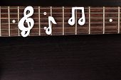 image of clefs  - Electric guitar deck with paper treble clef on dark background - JPG