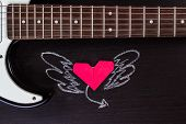 foto of heart sounds  - Electric guitar deck and paper heart with painted wings on dark background - JPG