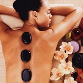 stock photo of backbone  - Adult woman relaxing in spa salon with hot stones on body - JPG