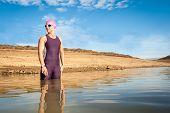 stock photo of dam  - Athletic female triathlete entering a dam in preparation for her swim - JPG