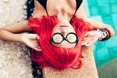 stock photo of wig  - Beautiful woman with red wig hair in black bikini and sunglasses relaxing beside a swimming pool - JPG