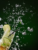 image of mojito  - Fresh mojito drink with ice cubes and splashes on black background - JPG