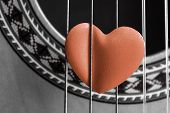 picture of heart sounds  - A red love heart on a black and white guitar - JPG