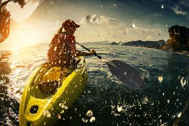 stock photo of kayak  - Young lady paddling the kayak in the sea with lots of splashes - JPG