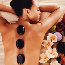 stock photo of stone-therapy  - Adult woman relaxing in spa salon with hot stones on body - JPG