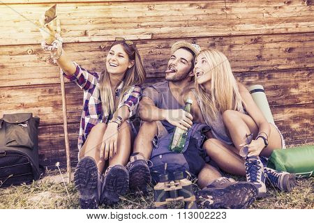 group of smiling friends taking funny selfie with smart phone