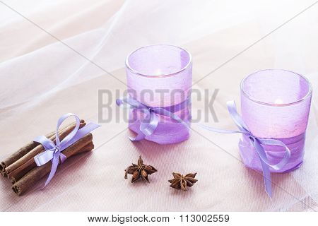 Two aromatic candles in glass candlesticks with lavender paper, cinnamon and anise on table close up