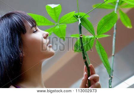 Girl with green leaves in garden