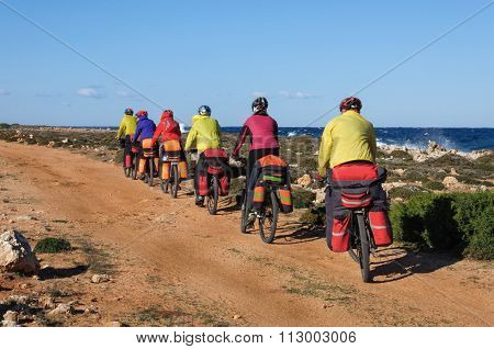 group of cyclists riding sandy beach mountain bike with backpack.