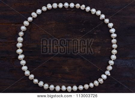 pearls string circle shaped top view old wood background