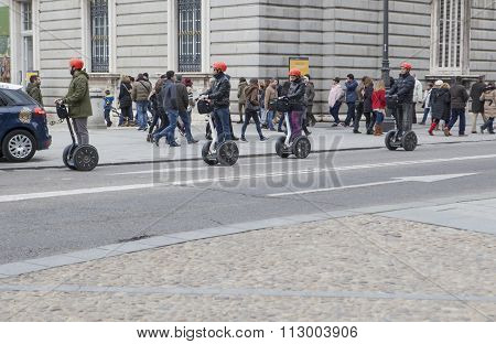 Tourists Sightseeing On Segway Tour Of Madrid, Royal Palace, Spain