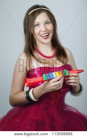 Cheerful Young Female Laughing And Holding A Toy Fife