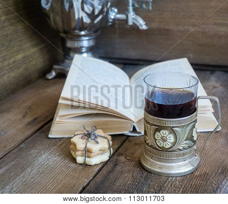 Book, Cookies And Tea In Coaster On Wooden Background