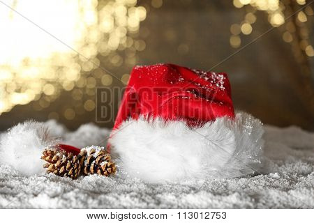 Santa Claus red hat with pine cones on the artificial snow against golden background, close up