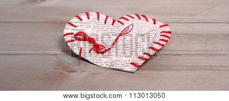 The Heart Which Is Cut Out From A Slice Of The Newspaper And Sewed By Red Threads On Gray Boards