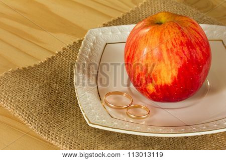 Wedding rings and red ripe Apple