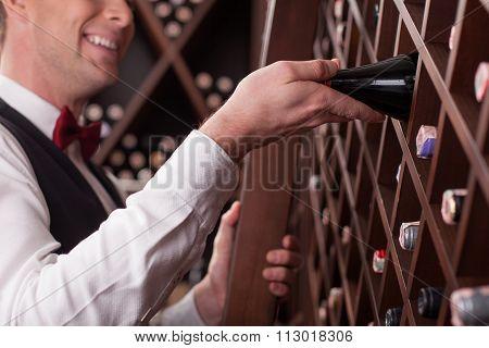 Skillful wine waiter is choosing perfect drink