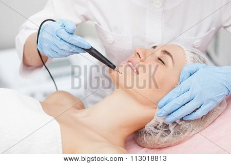 Skillful female beautician is curing her patient
