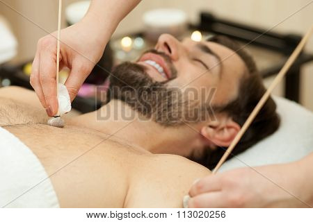Attractive guy is getting massage at beauty salon