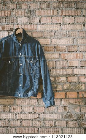 blue denim jacket on the brick backround