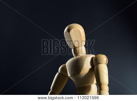 Sad human wood manikin against dark background